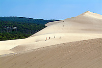 Tourists walking over the Great Dune of Pyla with the Landes forest visible in the background, France.