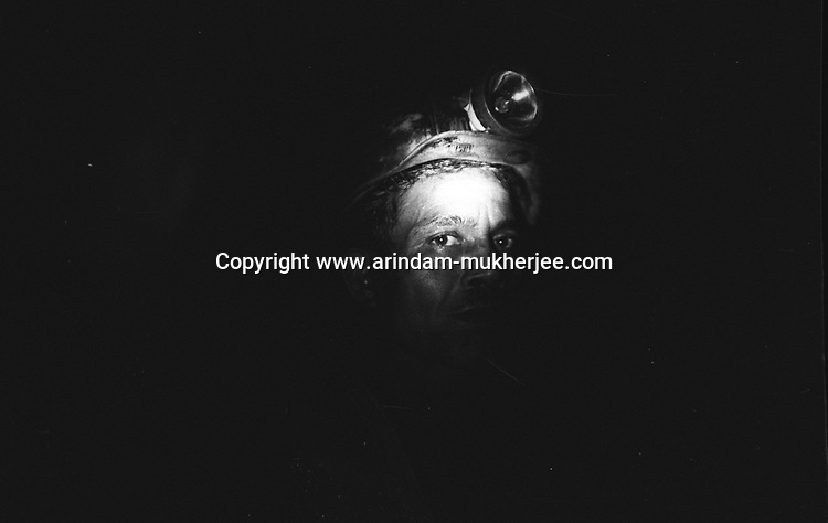 A miner wearing a headlamp defective and useless. The lamp stopped working while he was deep inside the underground mine. The head lamps are the only source of light for the miner inside. North Searsole Coliery in Ranigunj, West Bengal, India. Arindam Mukherjee
