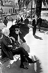 Two gay men sitting on park bench sheltering from the sun under an umbrella San Francisco California USA 1971. .