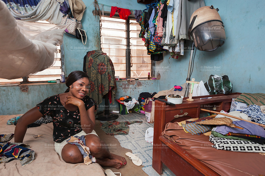 Nigeria. Enugu State. Enugu. A smiling Igbo woman seats on her  bed in the bedroom which she shares with her sick mother. Flip-flops are a type of sandal, typically worn as a form of casual wear. They consist of a flat sole held loosely on the foot by a Y-shaped strap known as a toe thong that passes between the first and second toes and around both sides of the foot or can be a hard base with a strap across all the toes (these can also be called sliders). Enugu is the capital of Enugu State, located in southeastern Nigeria.15.07.19 © 2019 Didier Ruef