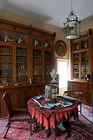 Blue and white dishes with antique spoons are displayed on a round table in the small library