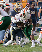 Pitt defensive back Jordan Whitehead (9) tackles Miami running back Joseph Yearby. The Miami Hurricanes football team defeated the Pitt Panthers 29-24 on  Friday, November 27, 2015 at Heinz Field, Pittsburgh, Pennsylvania.