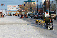 Matts Pettersson runs down Front Street on his way toward the finish line in Nome on Thursday March 19, 2015 during Iditarod 2015.  <br /> <br /> (C) Jeff Schultz/SchultzPhoto.com - ALL RIGHTS RESERVED<br />  DUPLICATION  PROHIBITED  WITHOUT  PERMISSION