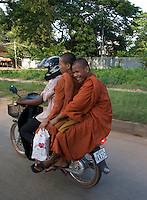 Siem Reap street scene, three Monks on the back of a Motor Bike, Cambodia