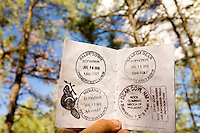 Photo story of Philmont Scout Ranch in Cimarron, New Mexico, taken during a Boy Scout Troop backpack trip in the summer of 2013. Photo is part of a comprehensive picture package which shows in-depth photography of a BSA Ventures crew on a trek.  In this photo a Boy Scout reviews several of the passport stamps in his Philmont passport book, in he backcountry at Philmont Scout Ranch.   <br /> <br /> The  Photo by travel photograph: PatrickschneiderPhoto.com