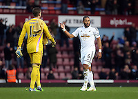 Sunday 07 December 2014<br /> Pictured: Ashley Williams of Swansea (R) asks his team mates to applaud their away supporters at the end of the game<br /> Re: Premier League West Ham United v Swansea City FC at Boleyn Ground, London, UK.