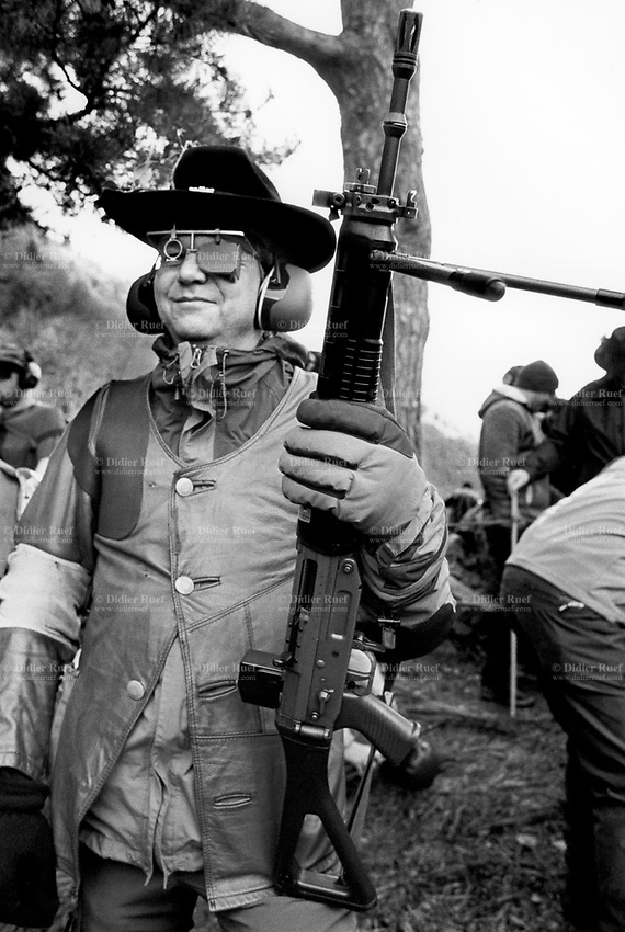 """Switzerland. Canton Uri. Rütli. A competitor and member of the riflemen's association holds his automatic or semi-automatic assault rifle SG 550 during the Rütlischiessen. Rütli or Grütli is a mountain meadow overlooking the lake Lucerne where the oath of the Rütlischwur for the forming of the Old Swiss Confederacy is said to have occurred as the legendary turning-point in the pursuit of independence. To commemorate this historic event, the riflemen's association of Lucerne organized the Rütli rifle match (Rütlischiessen) in 1862. It is held every year on the Wednesday before Martinmas (Saint Martin's Day). Thousand competitors from all over Switzerland fire their fifteen shots at targets arranged on a cliff. The SG 550 is an assault rifle manufactured by Swiss Arms AG (formerly Schweizerische Industrie Gesellschaft) of Neuhausen, Switzerland. """"SG"""" is an abbreviation for Sturmgewehr, or """"assault rifle"""". The rifle is based on the earlier 5.56mm SG 540 and is also known as the Fass 90 or Stgw 90. An assault rifle is a selective-fire rifle that uses an intermediate cartridge and a detachable magazine. Rütli (or Grütli in French) is a mountain meadow in the Seelisberg municipality of the Swiss canton of Uri. Here the oath of the Rütlischwur is said to have occurred, the legendary turning-point in the pursuit of independence. Every August 1, on the Swiss National Day, the oath is re-enacted to commemorate the forming of the Old Swiss Confederacy. Rütli is the birthplace of the Swiss Confederation. 9.11.2016 © 2016 Didier Ruef"""