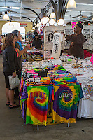 French Quarter, New Orleans, Louisiana.  T-shirt Vendor Offering Customer a Shirt in the French Market.