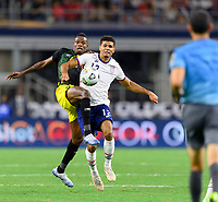 DALLAS, TX - JULY 25: Miles Robinson #12 of the United States and Cory Burke #9 of Jamaica battle for control of the ball during a game between Jamaica and USMNT at AT&T Stadium on July 25, 2021 in Dallas, Texas.