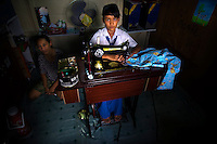 11 year old Aan Nuryani, fifth grade student at Kartini Emergency School, sits at a sewing machine at her slum home where she lives with her mother. Due to her skills as a seamstress, the 'Twin Teachers' bought her a sewing machine as a way to help her earn money for her family. Since the early 1990s, twin sisters Sri Rosyati (known as Rossy) and Sri Irianingsih (known as Rian) have used their family inheritance to set up and run 64 schools in different parts of Indonesia, providing primary education combined with practical skills to some of the country's most deprived children. .
