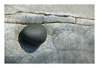 Rounded stone on granite