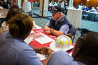 """Jim Ellis, an Air Force and Navy veteran from Danvers, Massachusetts, speaks with representatives of the Boston Fire Department at the Recovering Warrior Employment Conference at the Back Bay Event Center in Boston, Massachusetts, USA. Ellis said that he attended the conference to look for opportunities that fit his experience and expertise. """"I'd like to get in a position to help veterans,"""" he said.<br /> <br />  The employment conference was organized by Hiring Our Heroes and Wounded Warrior Project. Hiring Our Heroes is an initiative of the US Chamber of Commerce Foundation. Approximately 40 veterans registered for the event, during which they had interviews with a number of different regional and national employers, including GE, Bank of America, Uber, and others."""