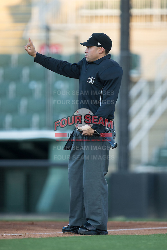 Home plate umpire David Martinez lets the pitcher know that he has two warm-up pitches left during the South Atlantic League game between the Hagerstown Suns and the Kannapolis Intimidators at Kannapolis Intimidators Stadium on May 4, 2016 in Kannapolis, North Carolina.  The Intimidators defeated the Suns 7-4.  (Brian Westerholt/Four Seam Images)