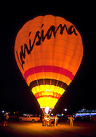 A hot air balloon illuminated at night reads, 'Louisiana'.