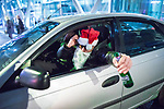 """© Joel Goodman - 07973 332324 . 15/12/2017. Manchester, UK. A man dressed as Santa Claus and holding a bottle of beer , leans out of the passenger window of a car on Deansgate . Revellers out in Manchester City Centre overnight during """" Mad Friday """" , named for historically being one of the busiest nights of the year for the emergency services in the UK . Photo credit : Joel Goodman"""