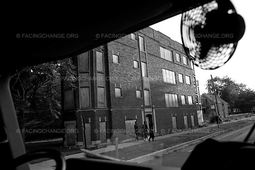 Chicago , Illinois <br /> USA<br /> July 2009<br /> <br /> Teens walk past border up houses in Chicago's South side. In 2009 President Barack Obama allocated $13.6 billion to the U.S. Department of Housing and Urban Development for affordable housing and community development.