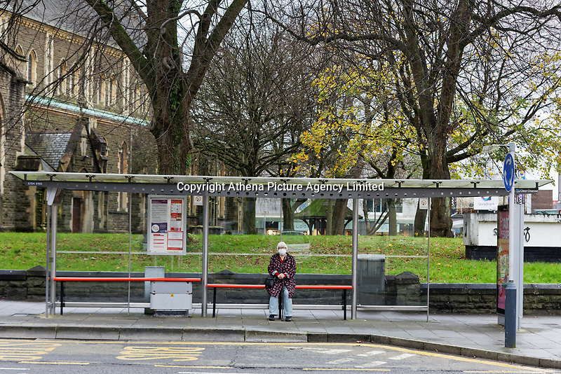 Pictured: A lone woman wearing a face mask sits at a bus stop by St Mary's Church in the city centre of Swansea, Wales, UK. Monday 30 November 2020<br /> Re: Pubs and restaurants will have to stop serving alcohol shut at 6pm from this Friday due to the Covid-19 Coronavirus pandemic, Wales, UK.
