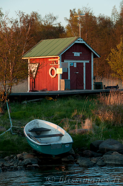 A beached rowboat rests for the evening at Säppi Island harbour cove in the Gulf of Bothnia, Finland.