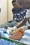 A technician fixing a mans toe in the ER of  Kibuye Hospital, Karongi District, Western Rwanda