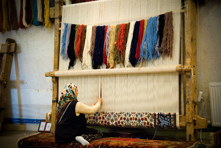 A woman weaving a rug using traditional methods, in Göreme, Turkey. Rug weaving in Anatolia first began with the arrival of the Turkish tribes from Central Asia, who settled in the region in the 11th century. More than a decoration, carpets have unique stories to tell in their designs, colors, of creation and localities where they are produced. It is tradition that only women weave carpets, while men repair or sell them.
