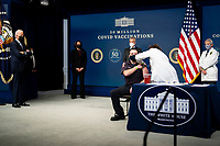 President Joe Biden looks on as a nurse gives a vaccine to Corey Hamilton, a firefighter EMT stationed at Engine Company 9 in Northwest DC, as he participates in an event commemorating the 50 million COVID-19 vaccine shot during a ceremony at the White House, Thursday, Feb. 25, 2021. <br /> Credit: Doug Mills / Pool via CNP /MediaPunch