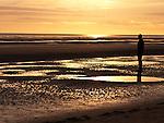 "Sunset on Crosby Beach Merseyside England.Antony Gormley's Iron Men look on.Part of  ""Another Place"" situated on Crosby Beach Merseyside England"