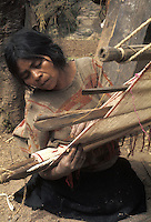 Latin America, Mexico, Oaxaca State, Mixtec Indian woman weaving cotton cloth using backstrap loom..