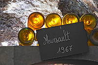 In the underground wine cellar: lying bottles in the treasure chamber where the oldest bottles are kept old bottles of Meursault 1967. White Burgundy wine vaulted vault ceiling with contrasting lights. Backlit backlight back light lit, Maison Louis Jadot, Beaune Côte Cote d Or Bourgogne Burgundy Burgundian France French Europe European