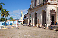 Cuba, Trinidad.  Entrance to the Church of the Holy Trinity on the right, facing the Plaza Mayor.  Bell Tower of the Church and Convent of San Francisco in the background, now the entrance to the Museo de la Lucha contra Bandidos (Museum of the Struggle against Counter-revolutionaries.