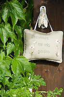 A padded fabric sign welcoming visitors to the garden hangs from a door handle in the shape of a fly