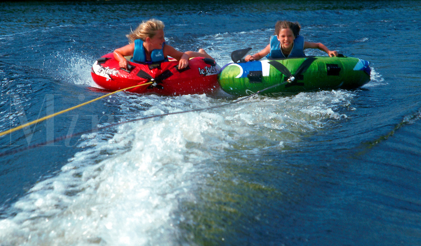 Two children ride on water raftss as they are pulled behind a boat.
