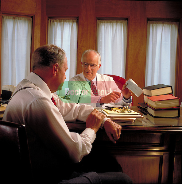 Doctor and male patient discuss EKG/ECG heart trace output tape