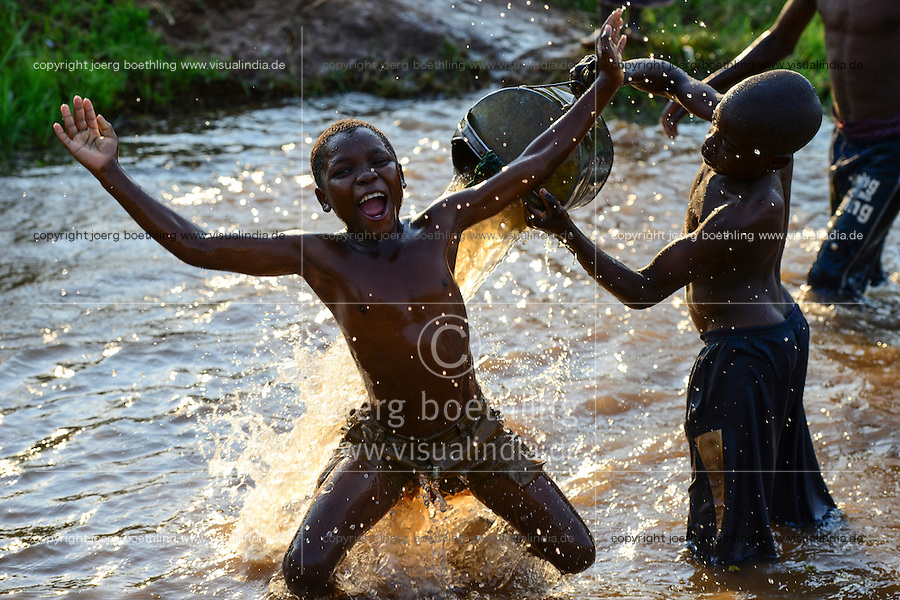 Malawi, Thyolo, children play in river with watering can for vegetable fields