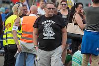 """Neonazis und Hooligans demonstrieren gegen Angela Merkel.<br /> Unter dem Motto """"Merkel muss weg"""" zogen ca. 1.200 am Samstag den 30. Juli 2016 mit einer Demonstration durch Berlin. Der Aufmarsch war vom einschlaegig bekannten Neonazi-Hooligan Enrico Stubbe angemeldet worden.<br /> Die Polizei hatte die Aufmarschroute der Rechten weitraeumig abgesperrt.<br /> Die Rechten forderten in Sprechchoeren immer wieder """"Nationalen Sozialismus! Jetzt!"""" (ein strafrechtlicher Trick, gemeint ist der Nationalsozialismus), beschimpften waehrend ihres Aufmarsches permanent Gegendemonstranten """"Wir kriegen euch alle"""" und """"Hurensoehne"""" und die Medienvertreter """"Luegenpresse"""". Mitarbeiter der Sicherheitsbehoerden erklaerten, dass es eindeutig ein rechtsextremer Aufmarsch gewesen sei bei dem sich keinerlei buergerliche Teilnehmer beteiligt haetten. Der Berliner Chef des Landesamt fuer Verfassungsschutz war persoenlich vor Ort um sich einen Eindruck zu verschaffen.<br /> Im Bild: Ein Demonstrationsteilnehmer mit einem T-Shirt auf dem ein """"Germane"""" abgebildet ist, der aus dem brennenden Reichstag emporsteigt.<br /> 30.7.2016, Berlin<br /> Copyright: Christian-Ditsch.de<br /> [Inhaltsveraendernde Manipulation des Fotos nur nach ausdruecklicher Genehmigung des Fotografen. Vereinbarungen ueber Abtretung von Persoenlichkeitsrechten/Model Release der abgebildeten Person/Personen liegen nicht vor. NO MODEL RELEASE! Nur fuer Redaktionelle Zwecke. Don't publish without copyright Christian-Ditsch.de, Veroeffentlichung nur mit Fotografennennung, sowie gegen Honorar, MwSt. und Beleg. Konto: I N G - D i B a, IBAN DE58500105175400192269, BIC INGDDEFFXXX, Kontakt: post@christian-ditsch.de<br /> Bei der Bearbeitung der Dateiinformationen darf die Urheberkennzeichnung in den EXIF- und  IPTC-Daten nicht entfernt werden, diese sind in digitalen Medien nach §95c UrhG rechtlich geschuetzt. Der Urhebervermerk wird gemaess §13 UrhG verlangt.]"""