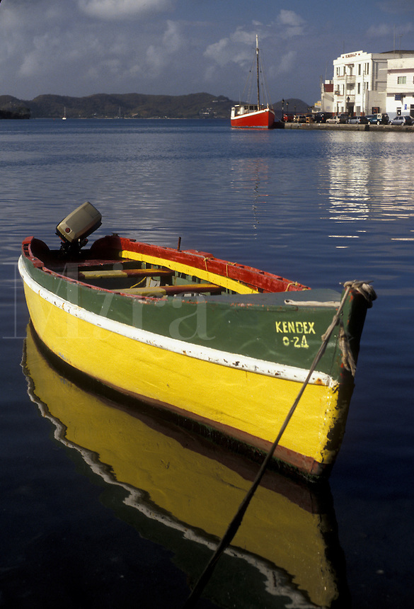 """AJ2531, Grenada, Caribbean, St. George's, Caribbean Islands, Green and yellow fishing boat reflects in the calm waters on the harbor of St. George's the capital city of the island of Grenada """"""""the spice isle"""""""" (a British Commonwealth member)."""