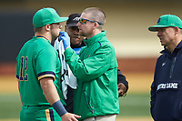 Notre Dame Fighting Irish trainer Scott Stansbury examines third baseman Niko Kavadas (12) after he was hit in the mouth with a throw during the game against the Wake Forest Demon Deacons at David F. Couch Ballpark on March 10, 2019 in  Winston-Salem, North Carolina. The Demon Deacons defeated the Fighting Irish 7-4 in game one of a double-header.  (Brian Westerholt/Four Seam Images)
