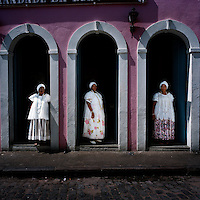 Three Irmanas (Sisters) stand at the entrance to the seat of the Irmandade da Boa Morte (Sisterhood of the Good Death). The Sisterhood began as a bank in 1823, founded by freed slaves, to finance the freedom of men, women and children still bonded by slavery. The community, which is still made up of the descendents of slaves, is one of the oldest and most respected worship groups for Candomble, the major African-based religion in Brazil. The sisterhood practices a syncretised worship that combines Candomble, Catholicism and Islamic elements. Thanks to their microcredit scheme, and the two hundred religious events they organise throughout the year, the Sisterhood have achieved a central role in regional society, preserving some of the traditional African values that slavery brought to Brazil.