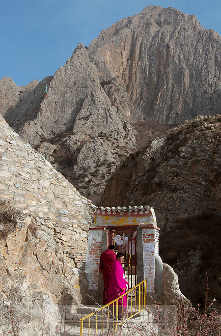 Two monks enter a monastery nestled deep in the mountains of the Qinghai-Tibetan Plateau. China.