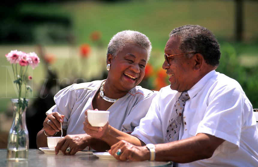 Black african american older grey retired couple outdoors relaxing at table and having fun
