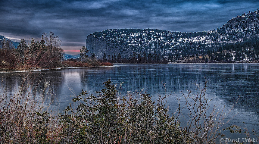 Fine Art Winter Scenic during the very early morning hours of McIntyre Bluff casting reflections onto the frozen ice of Vaseux Lake in British Columbia, Canada.