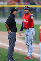 State College Spikes coach Ramon Ortiz (35) argues a call with umpire Dave Attridge during a game against the Batavia Muckdogs on July 28, 2013 at Dwyer Stadium in Batavia, New York.  Batavia defeated State College 10-5.  (Mike Janes/Four Seam Images)