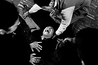 A Colombian woman, held by missionaries, screams of pain while being allegedly possessed by demons during the religious healing ritual performed by pastors of Misioneros Marianos church in Bogota, Colombia, 1 July 2013. Hundreds of Christian belivers, joined in nameless groups, gather every week in unmarked home churches dispersed in the city outskirts, to carry out prayers of liberation and exorcism. Community members and their religious activities are usually conducted by a charismatic pastor or preacher. Using either non-contactive methods (reading religous formulas from bible, displaying Christian symbols and icons) or rough body-pressure-points techniques and forced burping, a leading pastor commands the supposed evil spirit, which is generally believed to come from witchcraft, to depart a person's mind and body. The demon's expulsion often consists of multiple rites and may last for several months.