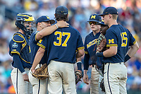 Michigan Wolverines head coach Erik Bakich (23) talks with pitcher Karl Kauffmann (37) on the mound against the Vanderbilt Commodores during Game 3 of the NCAA College World Series Finals on June 26, 2019 at TD Ameritrade Park in Omaha, Nebraska. Vanderbilt defeated Michigan 8-2 to win the National Championship. (Andrew Woolley/Four Seam Images)