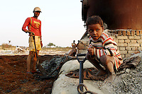 A child sits next to a vat used for burning leather trimmings on the outskirts of the town of Kanpur. The leather is burned, dried and then used as fertilizer and chicken feed.