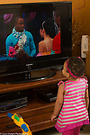 18 month old toddler girl at home, standing watching television