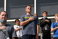 """Gabriel Miley (center) joins fellow students as they stand for a playing of the National Anthem, Thursday, September 9, 2021 at Tiger Stadium in Bentonville. """"I'm in the Navy JROTC program. We believe in honor, courage and commitment,"""" Miley said. """"I wanted to be a firefighter in the past, and I believe they are some of the best people out there because they knew they were going to die and they did it anyway."""" The district is educating students on the 9/11 attacks. Students completed 40 climbs up the home bleachers, the equivalent of the 110 stories (2200 stairs) of the Twin Towers. Check out nwaonline.com/210910Daily/ for today's photo gallery. <br /> (NWA Democrat-Gazette/Charlie Kaijo)"""