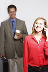 A young business woman on the phone with a coworker blurred in the background