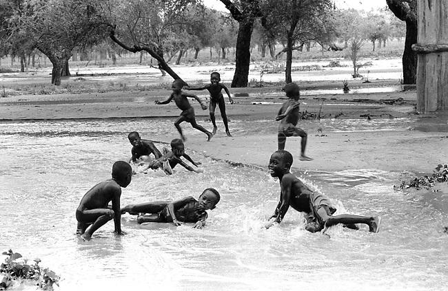 MALI, Dogon country, 1994<br /> Children playing in the water after the storm.<br /> MALI, Pays Dogon, 1994.<br /> Des enfants jouent dans la pluie après l'orage.<br /> © Bruno Cogez