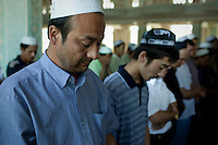 Uighur men pray at Yang Hang Mosque during Friday prayers in Urumqi. Due to the recent ethnic violence, Chinese authorities had tried to stop Friday prayers going ahead but at the last minute the doors to the mosque were opened.