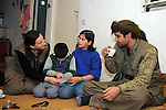 QANDIL, IRAQ:  Two PKK guerrillas play with children in a house in the Qandil mountains...The Kurdistan Workers' Party (PKK) is a pro-Kurdish party in Turkey deemed a terrorist group by the USA and the EU.  They are based in the Qandil mountains that make up the border between Iraq and Turkey...Photo by Kamaran Najm/Metrography